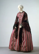 Silk satin dress edged with braid, with lace shawl