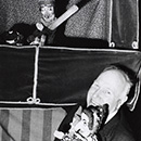 Percy Press Senior holding Judy and Baby outside his booth, and Mr Punch in his booth, in front of the crocodile.